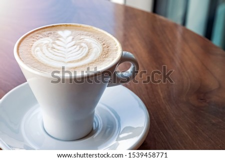 Fresh cappuchino or flat white coffee in a white cup with latte art close-up #1539458771
