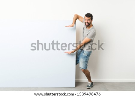 Young handsome man with beard holding a big blue empty placard holding copyspace to insert an ad #1539498476