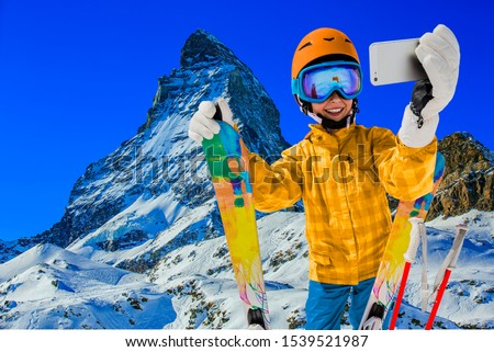 Teenager taking a selfie, girl taking a self portrait with mobile phone, sport skiing having fun on winter vacation. Royalty-Free Stock Photo #1539521987