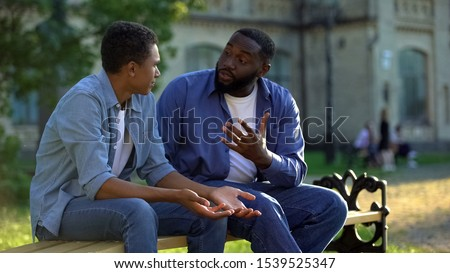 Father arguing teenage son sitting on campus bench, puberty age difficulties #1539525347