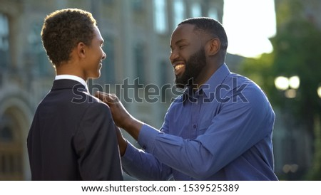 Excited african man feeling proud of young son in prom suit, college graduation #1539525389