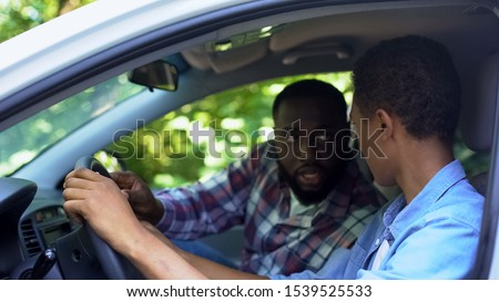 Male instructor teaching teen how to drive car, automobile school, license exam #1539525533