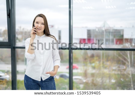 A woman in a white shirt stands by the window and talks on the phone. European girl is calling on a smartphone and smiling. #1539539405
