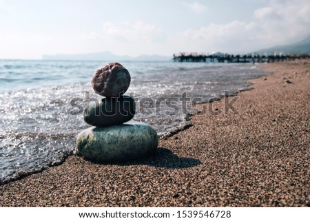 Stack of zen stones on beach near sea. Tower of spa rocks on sand at ocean. Balanced pebbles outdoors on sunny summer day. Oriental calm and harmony symbol. Wellness and tranquility concept #1539546728