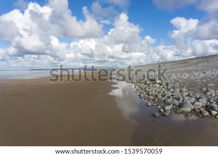 Westward Ho beach , rock pools and naturally formed pebble ridge in North Devon Royalty-Free Stock Photo #1539570059