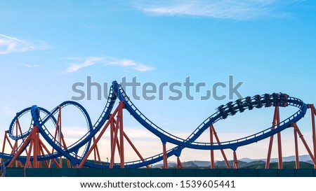 CLOSE UP: Cool shot of a roller coaster driving into a twister on a sunny spring evening. Thrill-seeking tourists ride an exciting roller coaster in an amusement park in beautiful Los Angeles. #1539605441