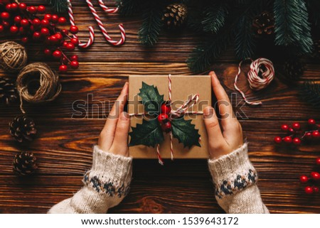 Christmas gift. Congratulations.Top wiew of woman holding traditional decorated gift box. Wooden table with cane,fir branches,fir cone, and berries #1539643172