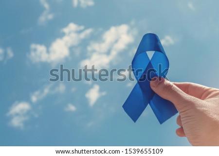 Hand holding blue ribbon on blue sky background , Prostate Cancer Awareness, Movember Men health awareness, November blue, International Men's Day, world diabetes day #1539655109