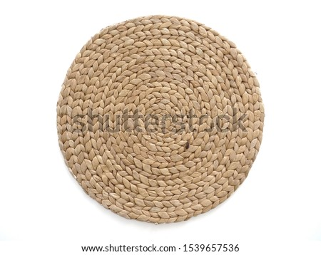 Top view texture of handmade round beige wicker tablecloth surface isolated on white background; Close-up of single oval water mat of water hyacinth fabric. Rustic appearance Heat-resistant. #1539657536