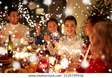 winter holidays and people concept - happy friends with sparklers celebrating christmas at home feast over snow #1539749936