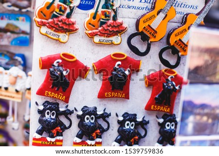 View of traditional tourist souvenirs and gifts from Spain, Alicante, Valencia with toys, bull figures, flamenco dancer dolls, fridge magnets with and key ring keychain, in local vendor souvenir shop  #1539759836