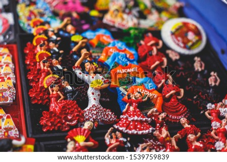 View of traditional tourist souvenirs and gifts from Spain, Alicante, Valencia with toys, bull figures, flamenco dancer dolls, fridge magnets with and key ring keychain, in local vendor souvenir shop  #1539759839
