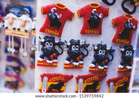 View of traditional tourist souvenirs and gifts from Spain, Alicante, Valencia with toys, bull figures, flamenco dancer dolls, fridge magnets with and key ring keychain, in local vendor souvenir shop  #1539759842