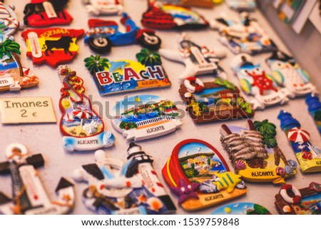 View of traditional tourist souvenirs and gifts from Spain, Alicante, Valencia with toys, bull figures, flamenco dancer dolls, fridge magnets with and key ring keychain, in local vendor souvenir shop  #1539759848