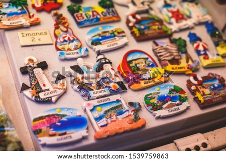 View of traditional tourist souvenirs and gifts from Spain, Alicante, Valencia with toys, bull figures, flamenco dancer dolls, fridge magnets with and key ring keychain, in local vendor souvenir shop  #1539759863