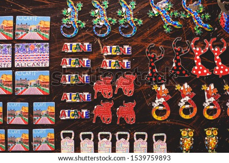 View of traditional tourist souvenirs and gifts from Spain, Alicante, Valencia with toys, bull figures, flamenco dancer dolls, fridge magnets with and key ring keychain, in local vendor souvenir shop  #1539759893