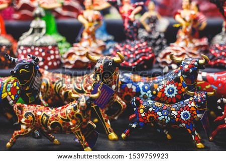 View of traditional tourist souvenirs and gifts from Spain, Alicante, Valencia with toys, bull figures, flamenco dancer dolls, fridge magnets with and key ring keychain, in local vendor souvenir shop  #1539759923