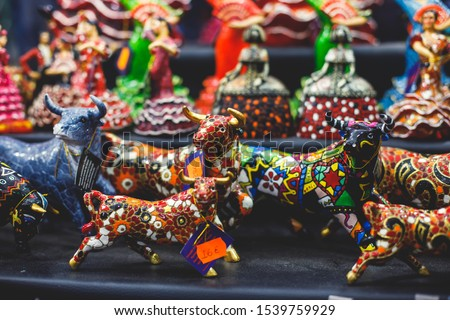 View of traditional tourist souvenirs and gifts from Spain, Alicante, Valencia with toys, bull figures, flamenco dancer dolls, fridge magnets with and key ring keychain, in local vendor souvenir shop  #1539759929