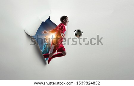 Kid footballer breaking through white paper. Mixed media #1539824852