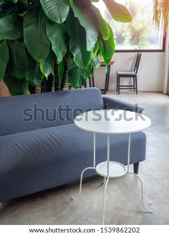 White round and curved steel table and grey fabric sofa near green leaves in cafe vertical style. #1539862202
