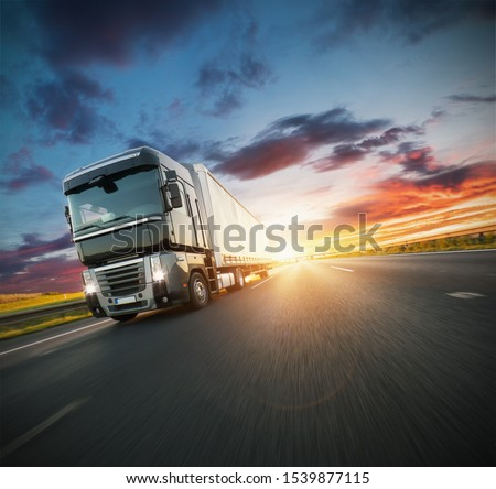 European truck vehicle on motorway with dramatic sunset light. Cargo transportation and supply theme. #1539877115
