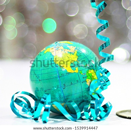 Celebrating New Years with a globe and stremers representing world wide celebrations no people stock photo #1539914447