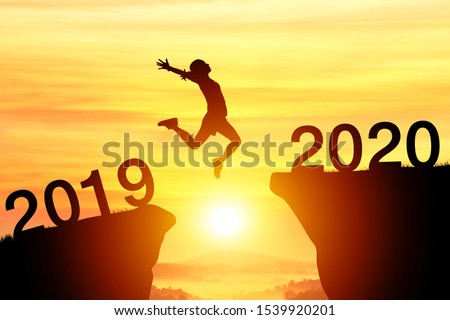 Silhouette sport woman jump through the gap between hill to the new year of 2019 to 2020 on sunset orange sky. happy New year concept.  #1539920201