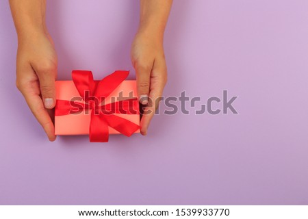 gift in female hands on a colored background top view. #1539933770