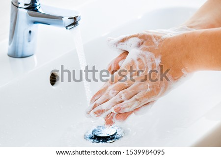 Woman use soap and washing hands under the water tap. Hygiene concept hand detail. #1539984095
