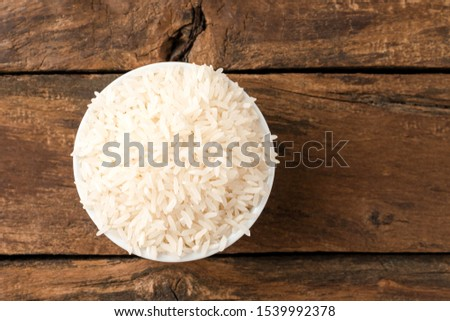 Uncooked white rice in bowl on rustic wooden table. Top view #1539992378