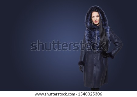 Beauty Fashion Model Girl in blue sheepskin Coat. Portrait of Beautiful Luxury Winter Woman in fur coat with hood on blue background with copy space #1540025306