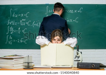 Studying in class as usual. Pretty class master conducting lesson in school. Smart teacher with class register sit at table while student writing formula on chalkboard. Laboratory class. #1540040840