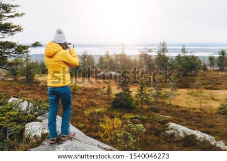Woman traveler in yellow jacket from back hike in autumn forest taking picture in Finland Lapland. Hiking travel and adventure. #1540046273