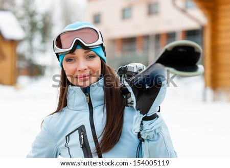 Portrait of woman wearing sports jacket and goggles who hands skis #154005119