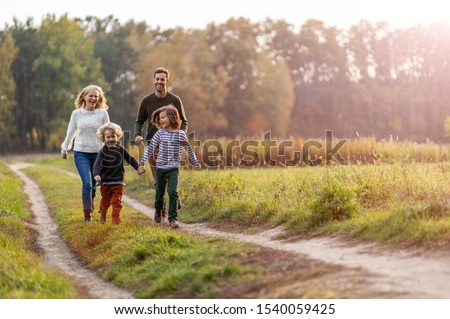 Young family having fun outdoors  Royalty-Free Stock Photo #1540059425