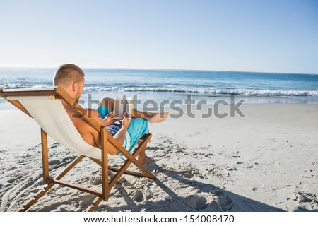 Smart handsome man reading a book on the beach #154008470