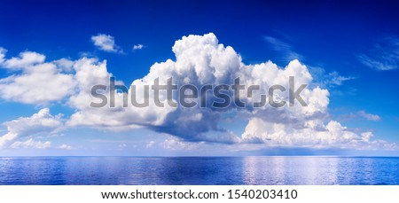 White cumulus clouds in sky over blue sea water landscape, big cloud above ocean panorama, horizon, beautiful tropical sunny summer day seascape panoramic view, cloudy weather, cloudscape, copy space Royalty-Free Stock Photo #1540203410