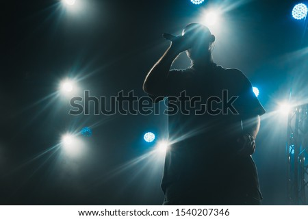A silhouette of a singer on the stage. Good-looking background, bright stage lights.  #1540207346