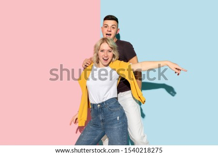 Young emotional man and woman in bright casual clothes posing on pink and blue background. Concept of human emotions, facial expession, relations, ad. Beautiful caucasian couple dancing together. #1540218275