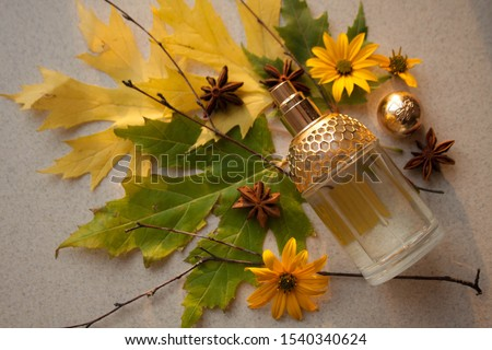 glass perfume bottle with a gold insert with autumn leaves. twigs, yellow flowers and anise stars #1540340624