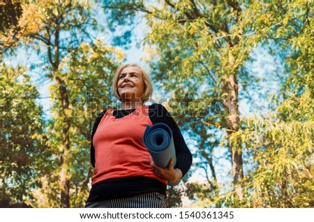 Old senior woman with yoga mat outdoors in woods going on training.Healthy lifestyle and exercise in retirement.Grey hair matured  female workout outdoors #1540361345