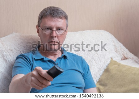 White middle-aged man in a blue t-shirt with a remote control from the TV. A man on a cozy sofa switches television channels #1540492136