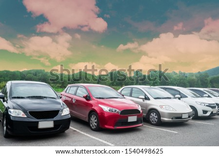 Cars parking in asphalt parking lot in a row with trees, colorful cloudy sky background in a park. Outdoor parking lot with fresh ozone, green environment of transportation and technology concept #1540498625