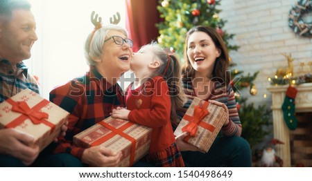 Merry Christmas and Happy Holidays! Grandma, grandpa, mum and child exchanging gifts. Parents and daughters having fun near tree indoors. Loving family with presents in room.                           #1540498649