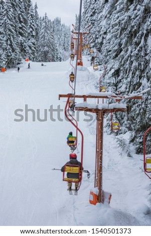 Chair ski lift next to slope for skis and snowboards. Skiers are sitting at old fashioned chair ski lift. Ski area in snowy high mountain. Sports and recreation concept. Selective focus. #1540501373