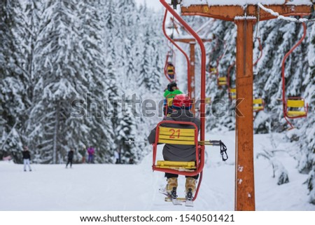 Skiers are sitting at old fashioned one chair ski lift.  Chair ski lift next to slope for skis and snowboards.  Ski area in snowy high mountain. Sports and recreation concept. Selective focus. #1540501421