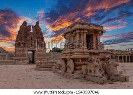 Ancient Hampi Monument Stone Chariot in the the Vittala Temple Complex with dramatic skies during sunset in Unesco Heritage Hampi town Karnataka #1540507046