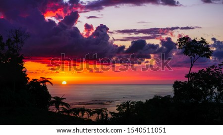 Spectacular sunset view in warm red, orange and purple tones. Beautiful colourful landscape scenery from highlander viewpoint of a setting sun in the background and silhouette of jungle trees in front #1540511051