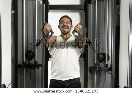 Young latin man at gym working triceps, chest, back, arms with pulley #1540525193