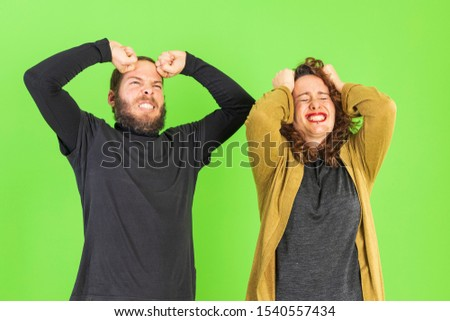 Young beautiful couple over green background annoyed and frustrated shouting with anger. anger concept #1540557434